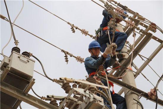 杨盛治和同事在电杆上接线作业。