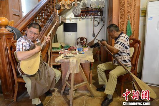 胡达白尔地和哥哥在为都塔尔调音。 勉征 摄
