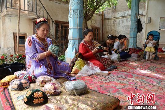 新疆喀什老城一家手工艺品合作社里,妇女们正在制作手工花帽。勉征 摄