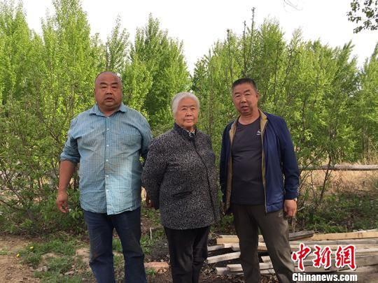 王建国(右)、王建军(左)和母亲朝玉香(中)合影。樊晓丽 摄