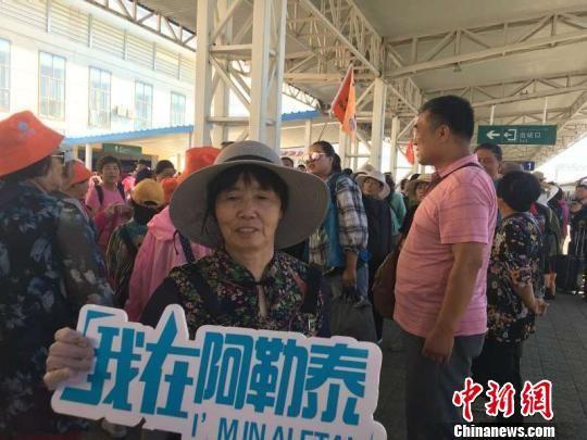 游客抵达新疆阿勒泰后拍照留念。 戴卫国 摄