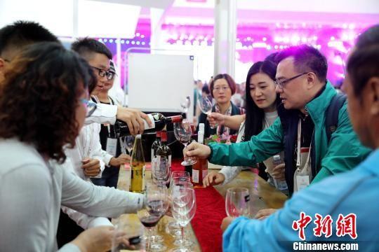 展览会现场,观众品尝参赛葡萄酒。 李佩珊 摄