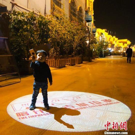 """28日夜晚,一位喀什市民带着自己的孩子游览""""喀什・印象""""一条街。小孩玩起了自拍。 朱景朝 摄"""