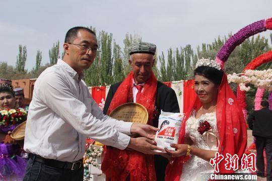 泽普县委常委、副县长,上海援疆泽普分指挥部副指挥丁铖惠给金婚老人送去喜糖和纪念品。 朱景朝 摄