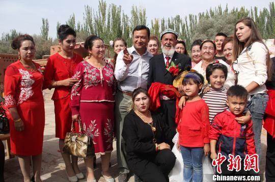今年90岁的的阿吾孜・阿迪力和他的妻子图迪罕・色依提结婚已经60年,有32个子孙。图为家人合影。 朱景朝 摄