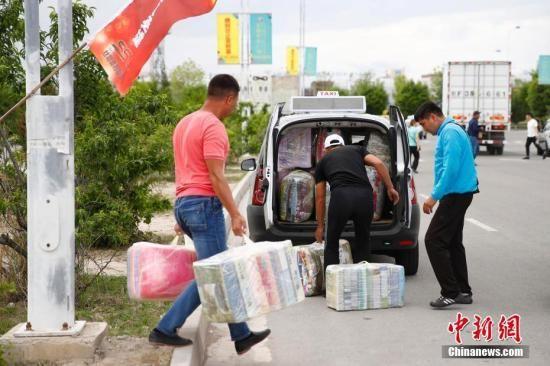 在中哈霍尔果斯国际边境合作中心,哈萨克斯坦顾客把货物塞满汽车。中新社记者 富田 摄