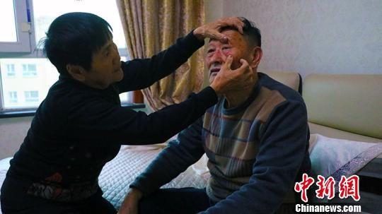 2018年,10月底夏忠惠老伴张胜利做完眼睛手术,夏忠惠帮助老伴查看眼睛。 王小军 摄