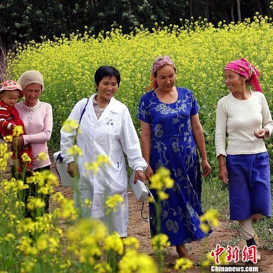 夏忠惠为村民看完病返回途中,与村民边聊边走。(资料图) 拜城县宣传部提供。 摄