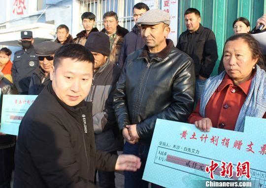 新疆昭苏县委常委、副县长何益龙为受助大学生家长代表捐款。 张雪峰 摄