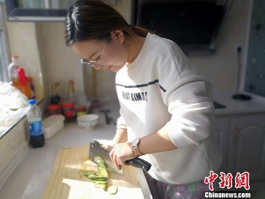 """衢州援建的乌什县""""人才公寓""""家电、厨具一应俱全,赵倩在厨房做饭。 王小军 摄"""