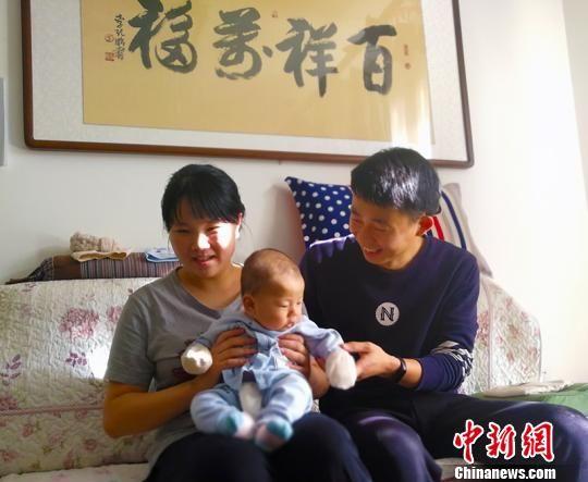 """入住乌什县""""人才公寓""""的任腾展、周佩兰夫妇在舒适的房间里带孩子。 王小军 摄"""