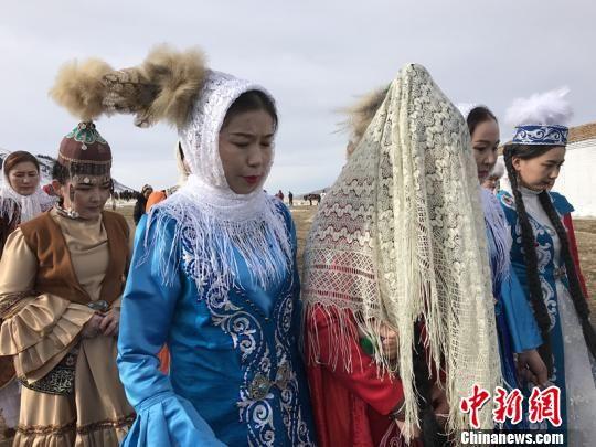 11月30日,生活在草原上的一对夫妻给游客演绎了哈萨克族婚礼,成都游客曾娟被邀请做伴娘, 朱景朝 摄