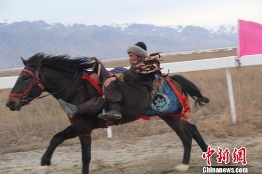 """""""马背上的民族""""哈萨克族骑手以雪山为背景,给游客展示了各种马上绝技。 朱景朝 摄"""