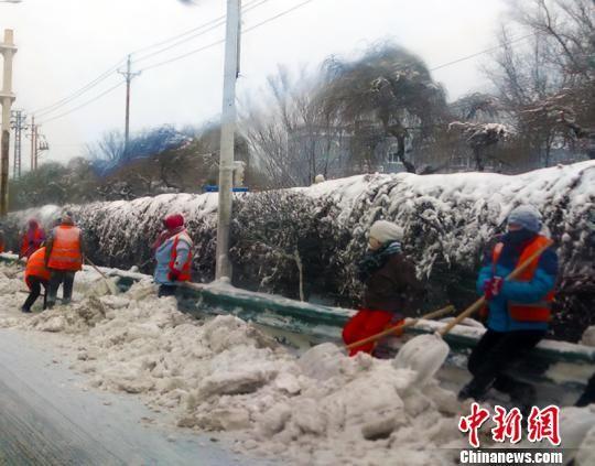 乌鲁木齐市西外环苏州路桥段保洁员等候卡车载雪。 王小军 摄