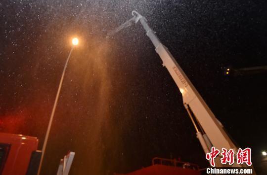 由于气温较低,举高类消防车辆在喷出雾状水后,落下瞬间结成了冰花。 洪文乐 摄