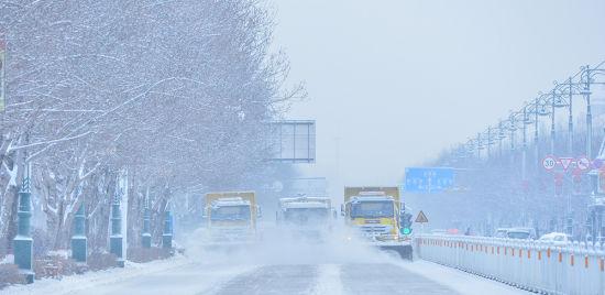 大型扫雪车在马路上进行清雪作业。 聂信华 摄
