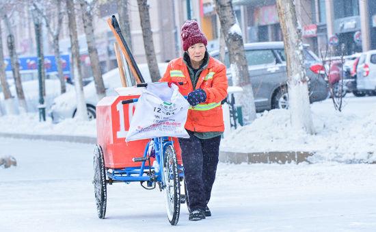 环卫工人推着三轮车赶往扫雪地点。 聂信华 摄