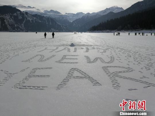"""巨大冰面,游客书写英文""""新年快乐""""。 王小军 摄"""
