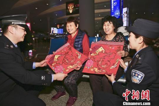 """青年民警将""""福""""字送给两位即将返回上海的老人,祝福她们健康幸福。 李国贤 摄"""