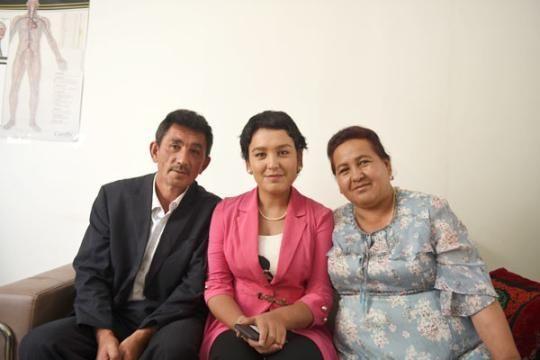 凯丽比努尔・库尔班江(中)及家人。潘迪/摄