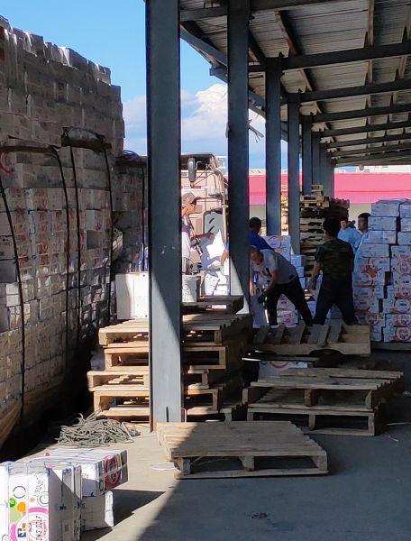 8月23日,在永盛物流公司仓储基地院内,工人们在忙着摆放待出口的商品。