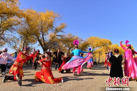 游客在金胡杨下翩翩起舞。 艾克 摄