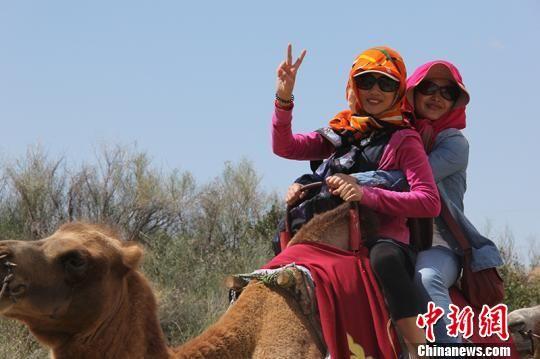 游客骑骆驼拍照。 杨东东 摄