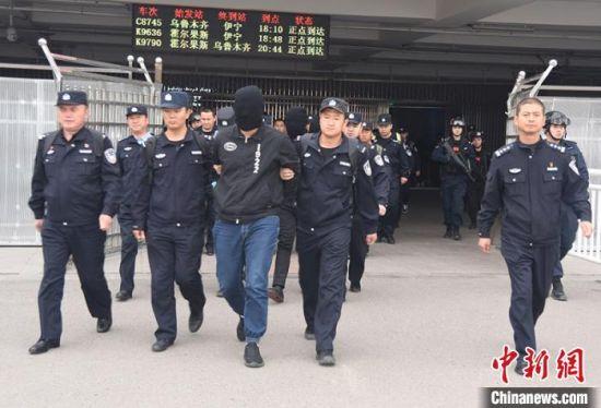 电信诈骗犯罪嫌疑人被民警押解出火车站。 杨文涛 摄