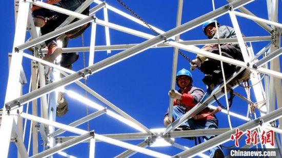 电力工人正在架设输电塔。 黄俊珲 摄