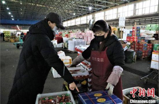 顾客在九鼎市场果品交易大厅购买水果。 杨涛 摄