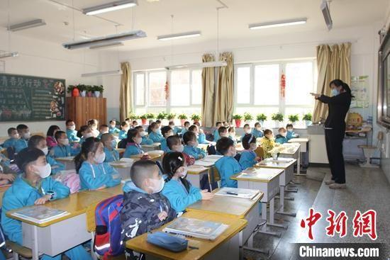 乌鲁木齐市第一小学开学第一天,学生们带着口罩听讲。 陶拴科 摄