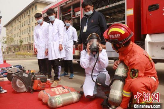 新疆阿克苏职业技术学院的学生们试戴空气呼吸器。 汪渝 摄