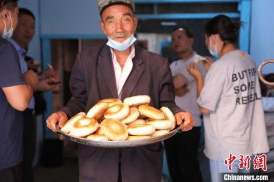 """表面金黄、口感酥脆的""""窝窝馕""""已销至上海、天津、广州等地。 故再丽努尔 摄"""