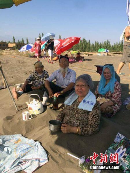 新疆吐鲁番最低气温创历史新高 沙疗受游客追捧