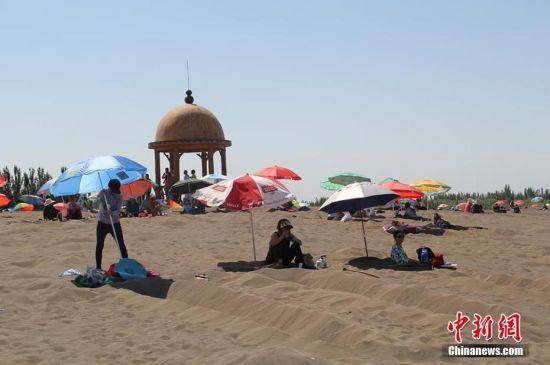 新疆吐鲁番进入高温模式 沙疗受游客追捧