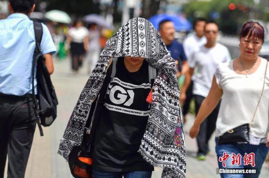 新疆乌鲁木齐高温达36摄氏度 民众顶烈日出行