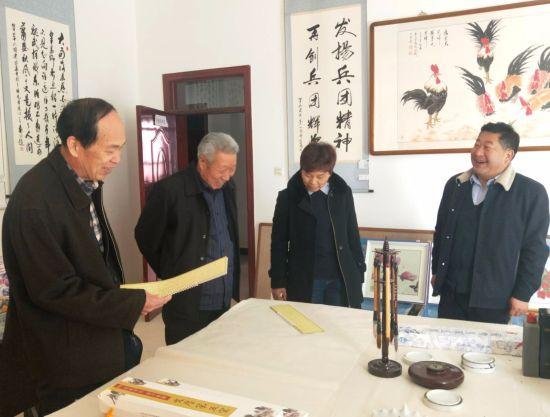 周德臣(左)一行参观该团老年书画活动室。