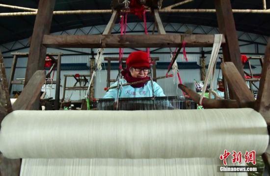 """图为""""织女""""在百年老纺机上工作。中新社记者 翟羽佳 摄"""